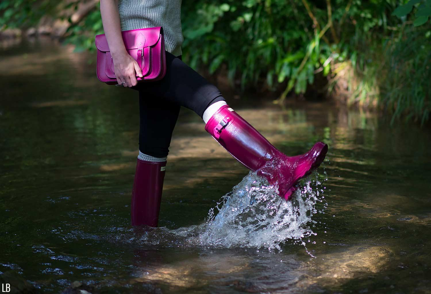 girl splashing in wellies water rain